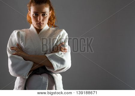 Confident Woman Wearing Karate Kimono with Crossed Arms