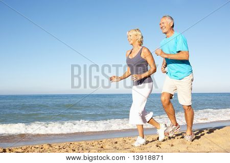 Senior Couple In Fitness Clothing Running Along Beach poster