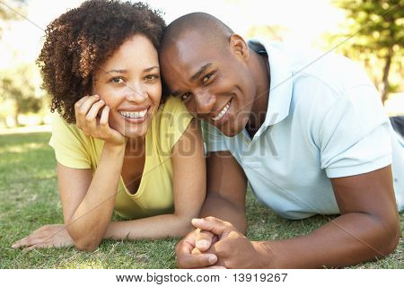 Portrait Of Young Couple Laying On Grass In Park