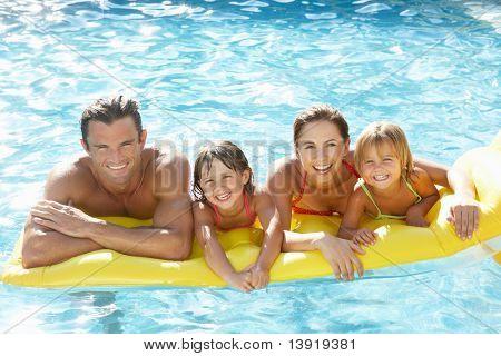Fiatal család, szülők, medence