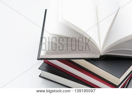 Hardcovered books on white background close up