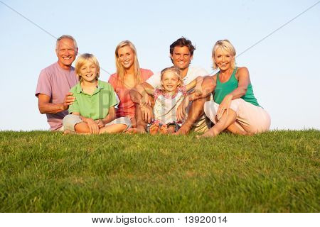 A family, with parents, children and grandparents, posing in a field