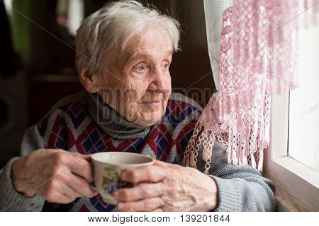 Elderly woman drinking tea sitting near the window.