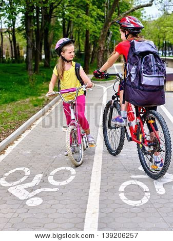 Bicycle girls wearing bicycle helmet and glass with rucksack ride on bicycle. Girls children cycling meet on white bike lane. Bike share program save money and time at city street.