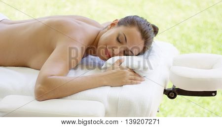 Disrobed woman lays belly down on table
