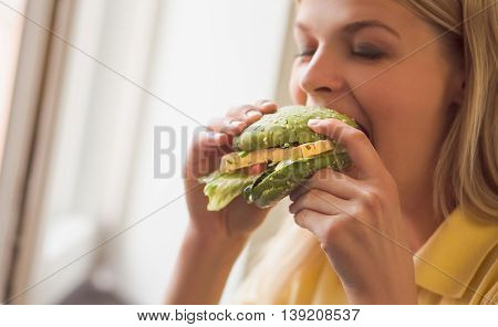 Pretty lady on vegan diet. Healthy food concept. Closeup image of blond woman eating vegan burger in vegan restaurant or cafe.