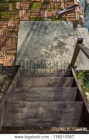 wooden stairs leading down to a concrete base