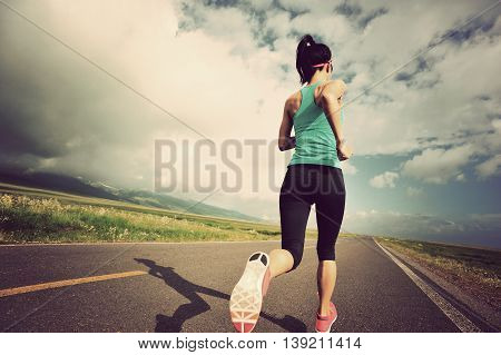 healthy finess young woman runner running on beautiful road