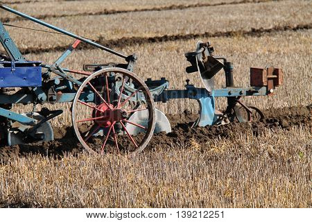 A Classic Agricultural Farming Plough Cutting a Furrow.