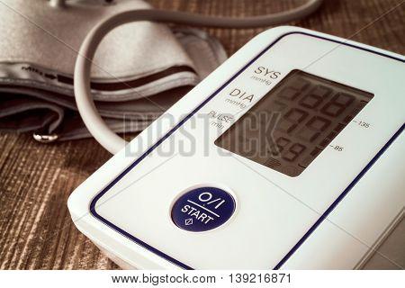 Digital blood pressure monitor on wooden background