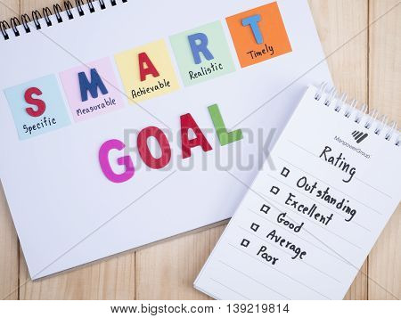Handwriting Performance Rating and SMART Goal on notebook with wood background (Business Concept)