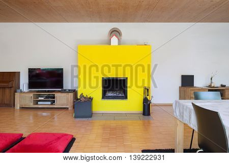 Interior of an eco house, living room with yellow fireplace