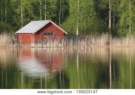 Boathouse At A Swedish Lake With Reflections
