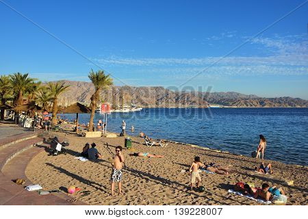 EILAT ISRAEL - MARCH 31 2015: Tourist relaxing on public beach in Eilat at sunset time famous international resort - the southest city of Israel