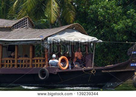 Allepey, Kerala, India, March 31, 2015: Unidentified indian man and tourists are sailing in houseboat on backwaters Allapuzha city