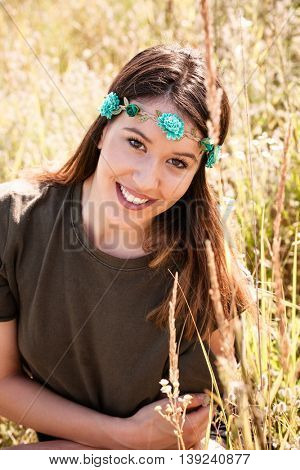 smiling young woman portrait with head band with flowers in summer meadow