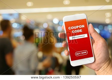 Woman hand holding smartphone against blur bokeh of mall background with word coupon code buy now