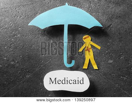 bandaged paper man under umbrella with Medicaid message