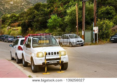 BALI GREECE - APRIL 29 2016: Rental all-wheel drive car Suzuki are parked on sloping street leading to the sea about office leasing transport. Resort village Bali Rethymno Crete Greece