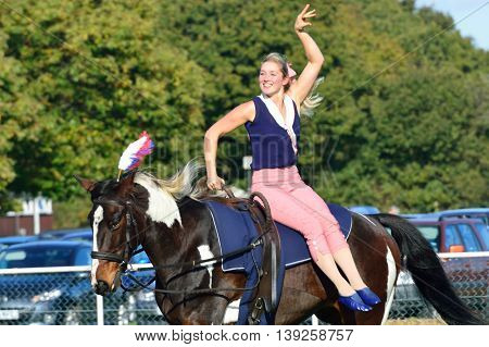 IPSWICH SUFFOLK UK 25 October 2014: East Anglia Equestrian Fair Horse gymnastic woman on side of horse