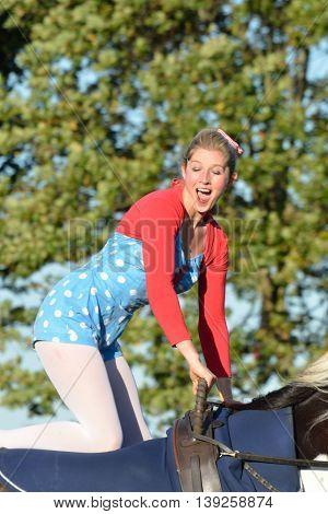 IPSWICH SUFFOLK UK 25 October 2014: East Anglia Equestrian Fair girl kneeling on horseback