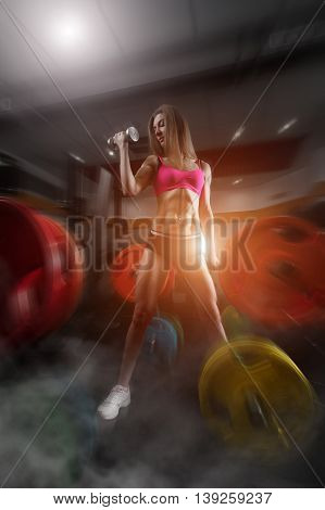 Fitness woman standing in a smoky gym. Fitness woman in the gym. fitness girl with dumbbell posing in the gym. Fitness - concept of healthy lifestyle. Perfect fitness body.