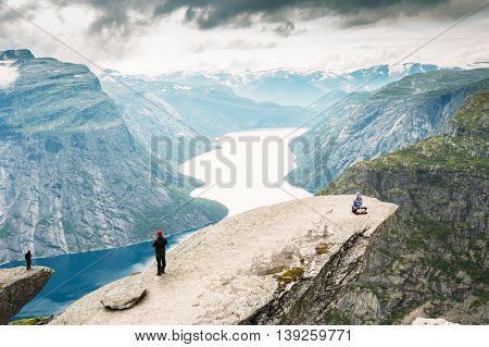 Odda, Norway - August 04, 2014: Young People Are Photographed Standing On A Rock Trolltunga - Troll Tongue In Norway. View From Rock Trolltunga - Troll Tongue.