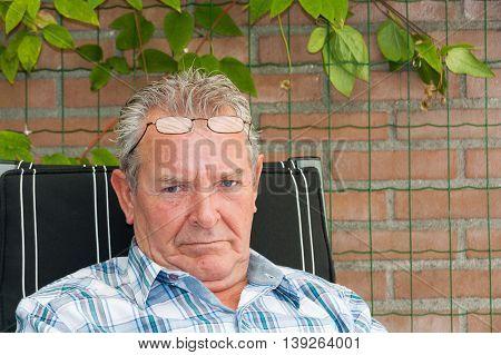 Grumpy Old Man Sitting Outside In His Garden