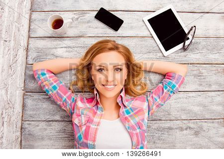 Top view photo of pretty woman lying on floor with tablet phone cup and glasses