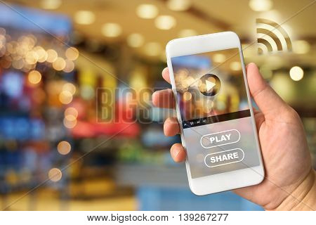 Woman hand holding smartphone against blur bokeh of shop background video ads concept