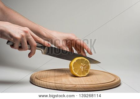Girl cuts frash lemon into slices on a cutting board.