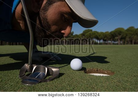 golf player blowing ball in hole. concept of cheating and success