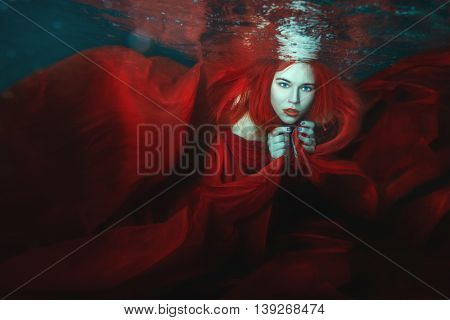Woman in a red dress swimming under water.