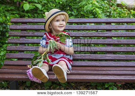 beautiful toddler girl sitting on a bench holding a flower