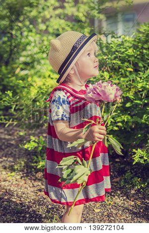 Beautiful little girl holding a flower in the garden