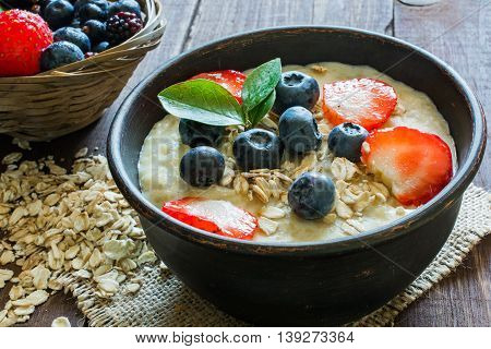 Oatmeal porridge in brown pottery bowl with ripe berries raspberries and blueberries in wicker bowl. healthy breakfast