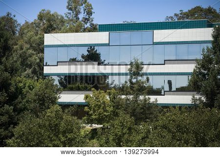 Office building with lots of glass windows nestled among the trees