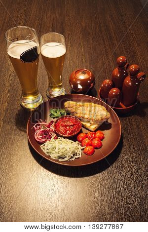 Pint of beer with tomatoes and a meat stake on the table bar in a pub.