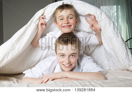 two boys hiding in bed under a white blanket or coverlet.