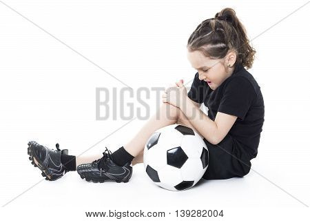 An injury girl with soccer ball isolated on white