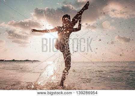 women splashes in water outdoor sunset ocean