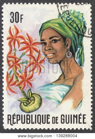MOSCOW RUSSIA - CIRCA JANUARY 2016: a stamp printed in GUINEA shows a woman in the traditional headdress and a plant Haemanthus sp. the series
