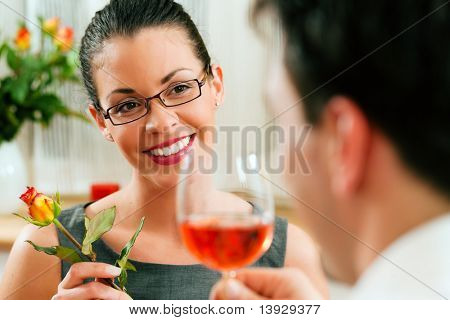 Young couple having romantic dinner � he is drinking rose wine