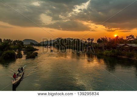 A longboat on the Mekong River as the sun sets in rural Laos