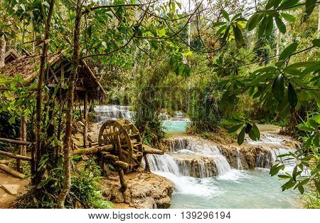 A water wheel at the pristine Kuang Si falls near Luang Prabang, Laos