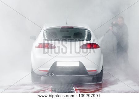 Automobile in car wash, water splatter background. Cleaness, care, hobby concept