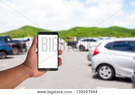 The Hand Of Man Hold Mobile Phone Over Blurred Car Parking With Bokeh Light Background