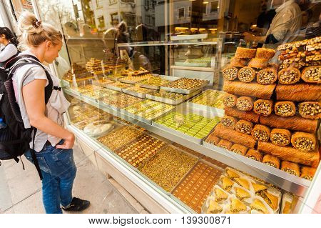 Showcase with Oriental sweets with nuts in assortment. Tourist female standing and looking in the window with oriental sweets on the streets of Istanbul. Shop with sweets. Travel Turkey.