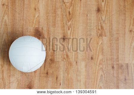 sport, fitness, game, sports equipment and objects concept - close up of volleyball ball on wooden floor from top