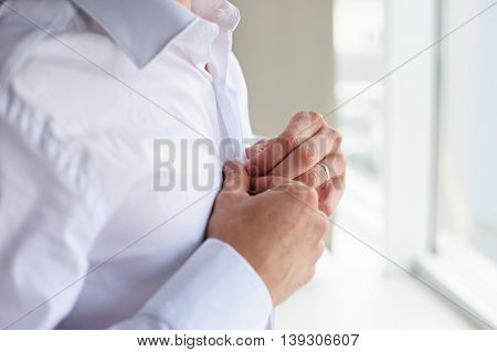 Man buttons shirt. Businessman adjusting his shirt buttons. Groom in the morning wears a white shirt to a wedding.